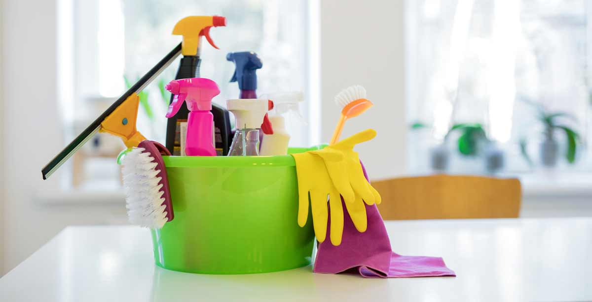 a variety of cleaning products and accessories in a green bucket