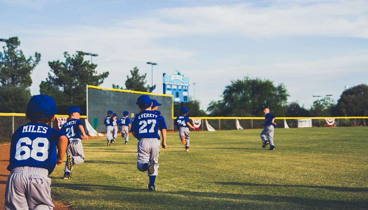 Children playing sports on a baseball field