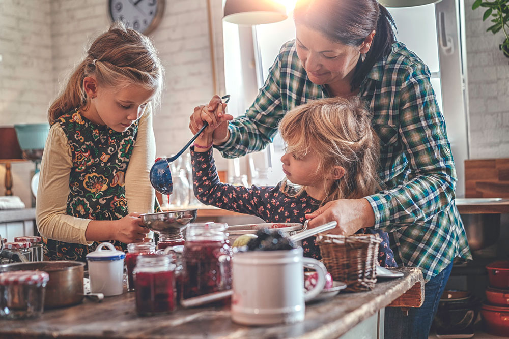 Mother and two daughters making fruit preserves in kitchen