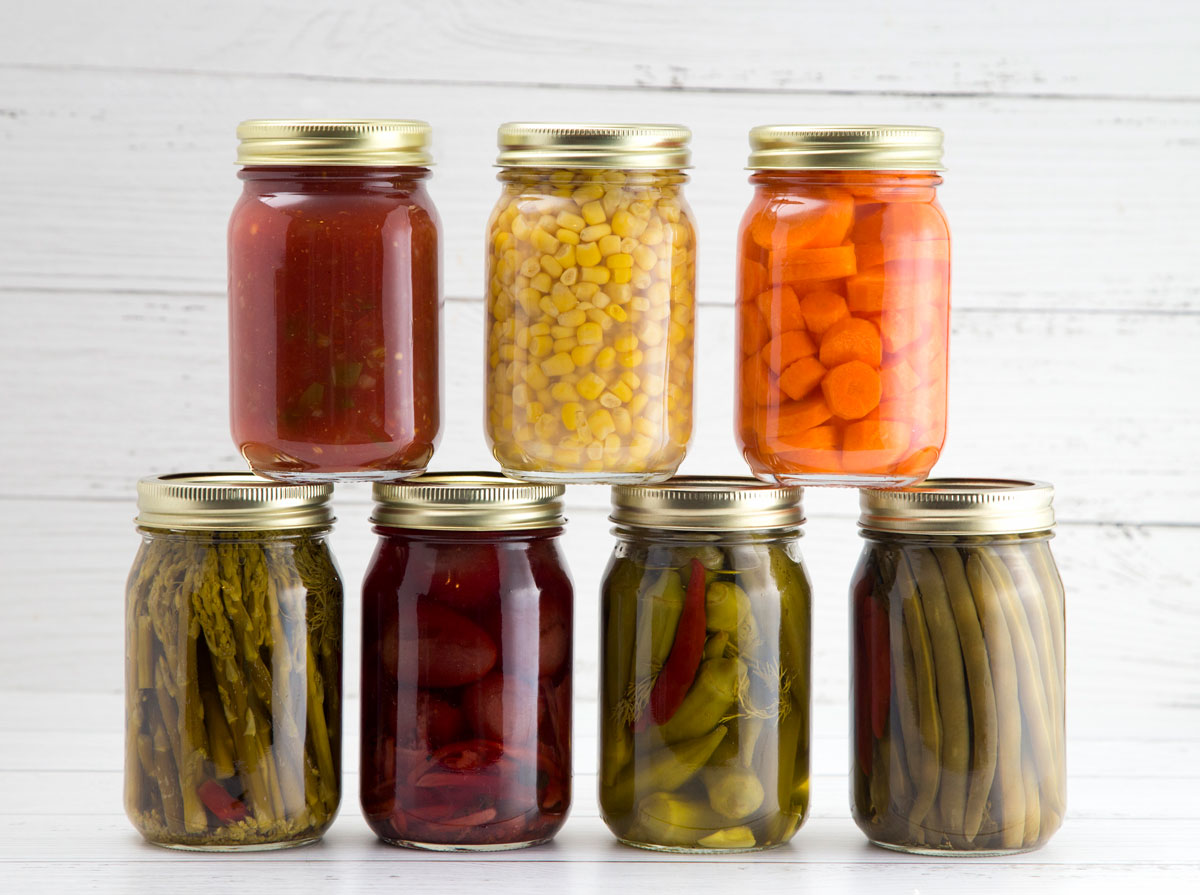 Photo of seven home-canned fruits and vegetables against a white backdrop