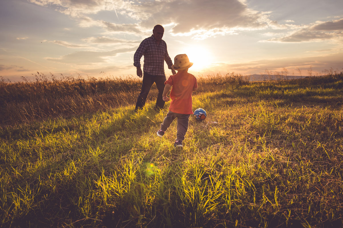 father-and-son-playing-soccer-in-a-field