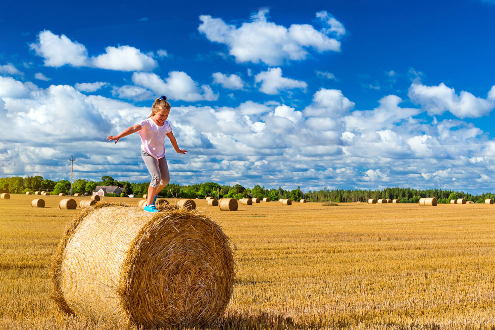 Child balancing on top of a bail of hay