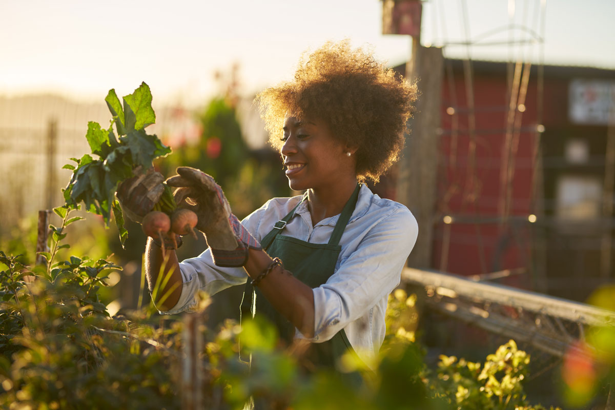 Woman gardening holding up vegetables
