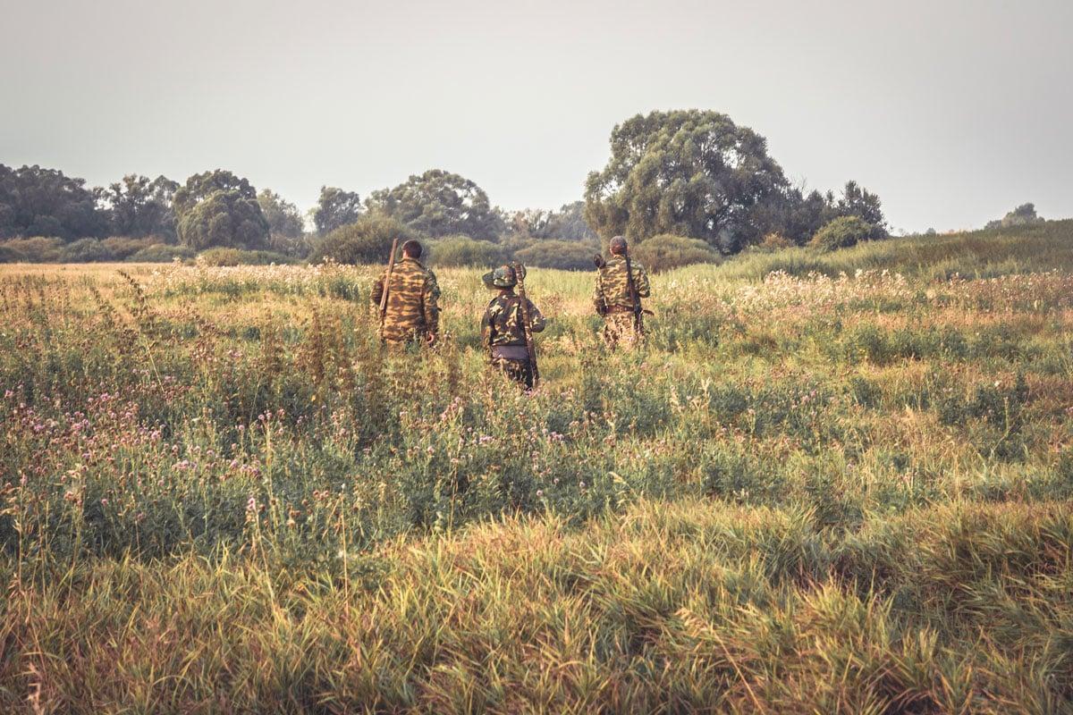 three men in camo in an open field