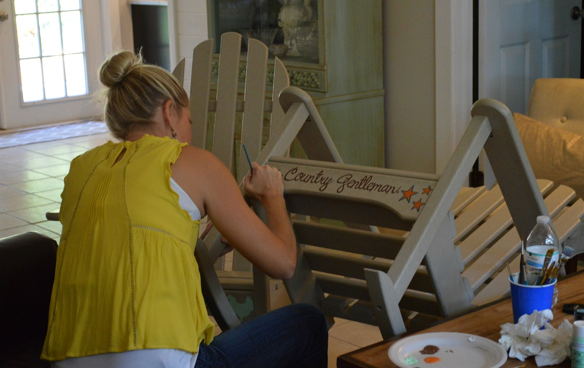 Artist paints rocking chairs for Sunbelt Ag Expo